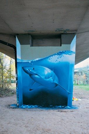 Emerging Belgian artist Smates transforms a concrete motorway pillar into a tank for a Great White shark, changing the mundane into the monumental.
