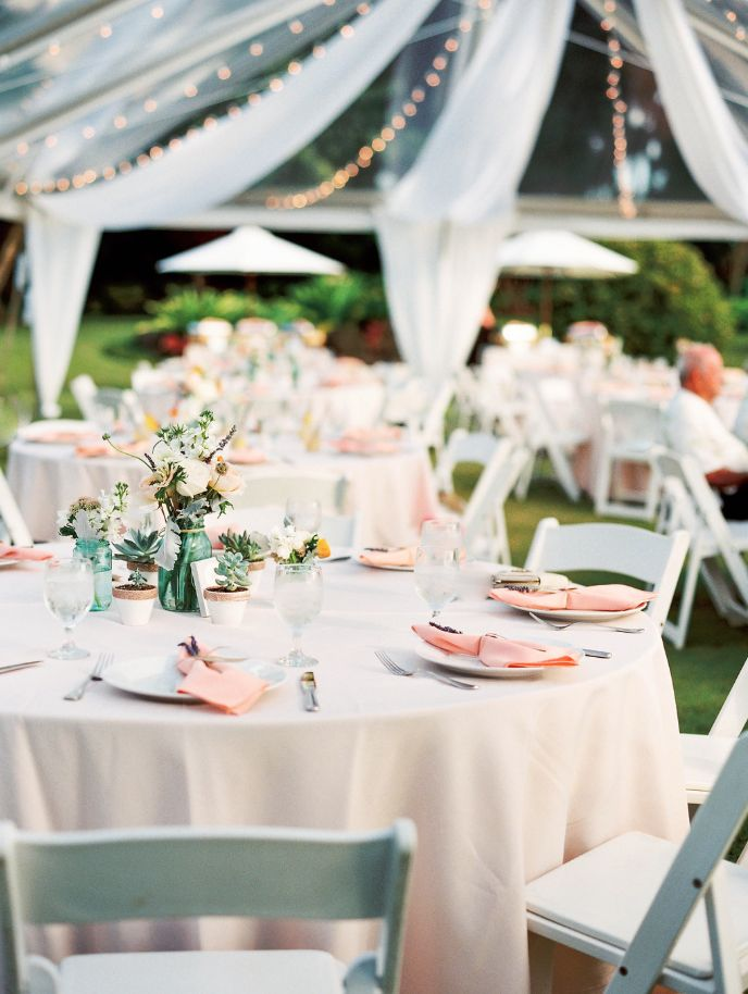 Round Guest Tables with White Resin Chairs under a Clear Top tent.  White Chinaware, Peach Polyester napkins, Ice Peach Polyester table linen