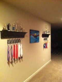 Long narrow space decorated with sports ribbons, medals, trophies and artwork-kids hallway