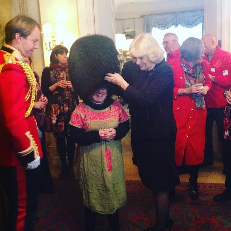It's a Clarence House #Christmas tradition for one of the Welsh Guards to help The Duchess of Cornwall and her guests from @helenanddouglashouse decorate our Christmas tree. Alice one of The Duchess's guests enjoyed trying on the traditional Welsh Guard hat!  by clarencehouse
