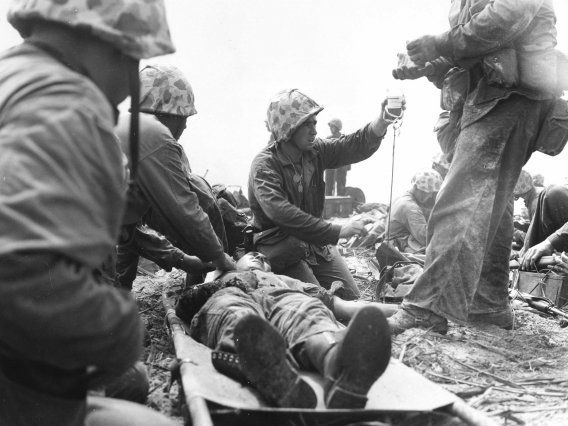This 1944 photo shows a Navy corpsman giving a wounded Marine blood plasma on an island in the Pacific. Marines captured the island in 24 hours with help from the heaviest naval and air bombardment ever at that time.