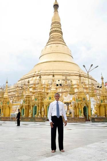 """To some, this is a snapshot and doesn't belong in this gallery of candid photographs. But to me, it evokes what the trip to Burma was all about. Here is the President of the United States, shoes and socks off in respect, posing as a tourist in front of the oldest pagoda in the world in a country that no U.S. President had ever been able to visit."""