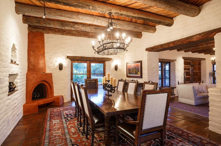 The heavy beams, Satillo tile and kiva fireplace make the dining room distinctly Southwestern. But the Persian rug (whose colors blend with the terra-cotta tile) and the dining chairs with the linen backs give the rustic a touch of luxe.
