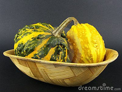 Couple of pumpkins in bamboo bowl on black background. latin name: Cucurbita pepo giromantia.