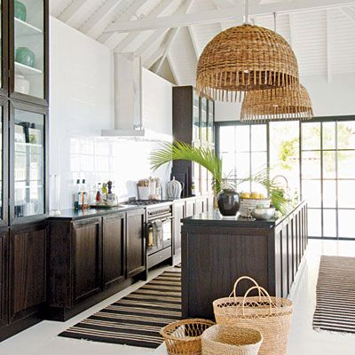 British Colonial elements in this kitchen, like the high ceilings & tall glass china cupboard & rattan pendent shades give this room an tropical feel.