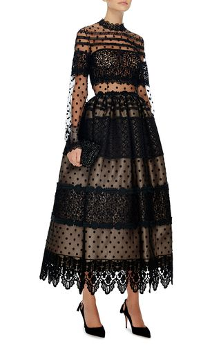 This long sleeve **Costarellos** dress is rendered in tulle with Chantilly and guipure lace applique and features an a-line silhouette with a mock neck, and a scalloped midi length hem.