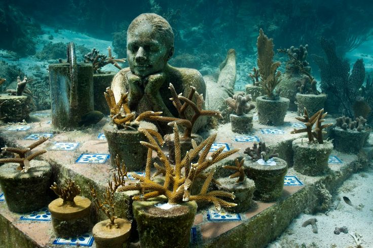 Among the MUSA Collection in Punta Nizuc, Mexico, A young girl can be seen lying on garden patio steps, surrounded by various plant pots. Ta...