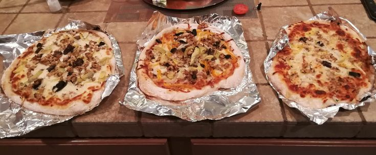 There blind pizzas We don't have a recipe we just mix flour just enough salt and activated yeast and water to make sure you got a nice sticky liquid dough. Topped with bell peppers olives chicken mushrooms and artichokes.