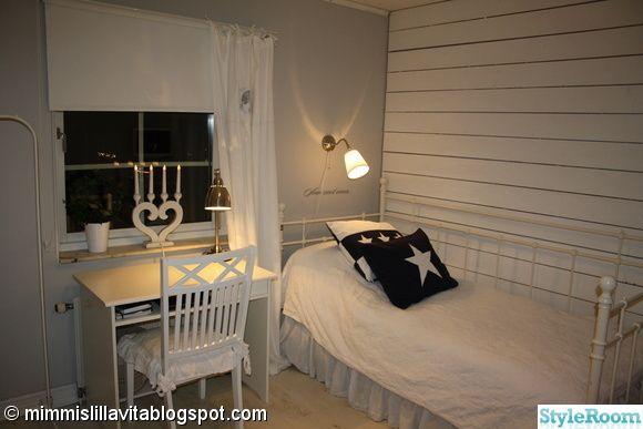 Sovrum med vit plankvägg.. Grå väggar med en plankvägg i vitt. Golvet är ett laminatgolv i vit ek.