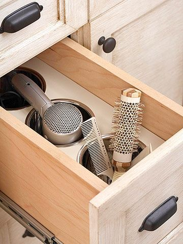 Customize Cabinets:  Here a deep drawer can safely hold a hot flat iron and other primping tools after use. Custom-fit stainless-steel canisters allow these beauty tools to cool safely inside the drawer as well as house brushes, combs, and a hair dryer. Need to do this in my daughters bathrooms!