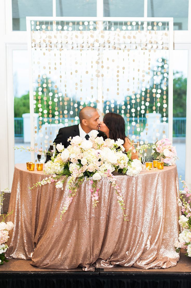Rina and Juan dined at a sweetheart table decorated in rose gold sequin linens and lush blooms. A confetti glitter backdrop was displayed behind the table. Venue: Los Coyotes Country Club Event Planner: CCLWeddings &...