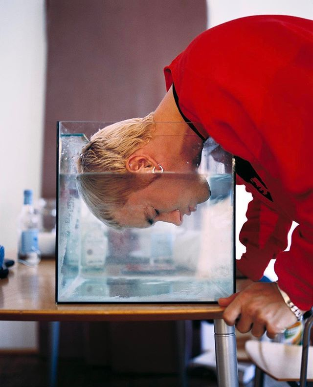 """Eminem, 1999: """"Especially with hip-hop, the way people tend to pose is pretty predictable, and I wanted something that was outside of that. This was just something I could do that would be a little surprising. I basically just told him, """"I want you to stick your head into the fish tank,"""" and he was like, """"Okay. You mean like this?"""" The funny thing was that he put his two cents in and asked that we put a bottle of tequila in the shot. If you look through the fish tank, you can see it."""" Chris…"""