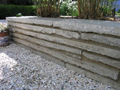 Long pieces of reused concrete slab have a new life in this attractive retaining wall. For the wall face, use the straight edges from recycled driveways and sidewalks. Pavement slabs like this have somewhat uniform thickness, good for stacking. www.ContainerWaterGardens.net