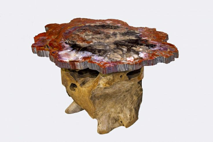 """Petrified wood Slice """"Cocktail"""" table on a Teak Base. Wonderful colors are displayed in the slice as in what we find in our desert Southwest. Tones of reds, mauve, charcoal grey and lovely calcite crystals. These colors spotlight decor in a magical way that brings warm tones into play creating an extraordinary statement in style! Enjoy a drink with friends while contemplating the life of a tree that is now a fossil."""