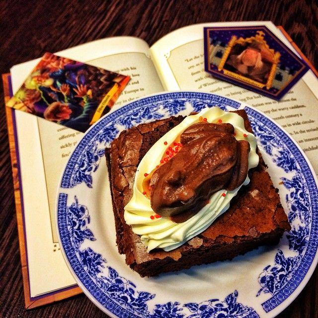 Chocolate Frog Mud pie  Γεύση: Το αγαπηµένο mud pie στην δική µας εκδοχή του σοκολατένιου βάτραχου από σοκολάτα γάλακτος µε µπαχαρικά σε φωλιά βουτυρόκρεµας και µια κουταλιά φυστικοβούτυρο στην µέση. Στοιχεία: Οι σοκολατένιοι βάτραχοι ήταν η «Κουκουρούκου» των µάγων. Οι µικροί µαθητές του Χόγκουαρτς έκαναν συλλογή τις κάρτες µαγικών διασηµοτήτων. Ο Ρον είχε ιδιαίτερα µεγάλη συλλογή όπως και τα αδέλφια του.