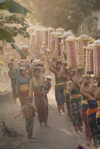 Women balance fruit and rice stacks on their heads in a procession.