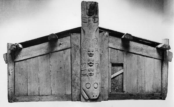 A mortuary house with a halibut frontal pole. The frontal pole is interesting for its use of a single crest figure that uses the flat carved slab style, referred to as having been an earlier style of frontal pole.