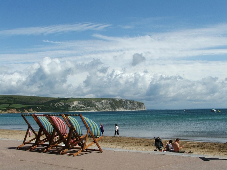 Colourful deckchairs line the coastline in Swanage, Dorset.
