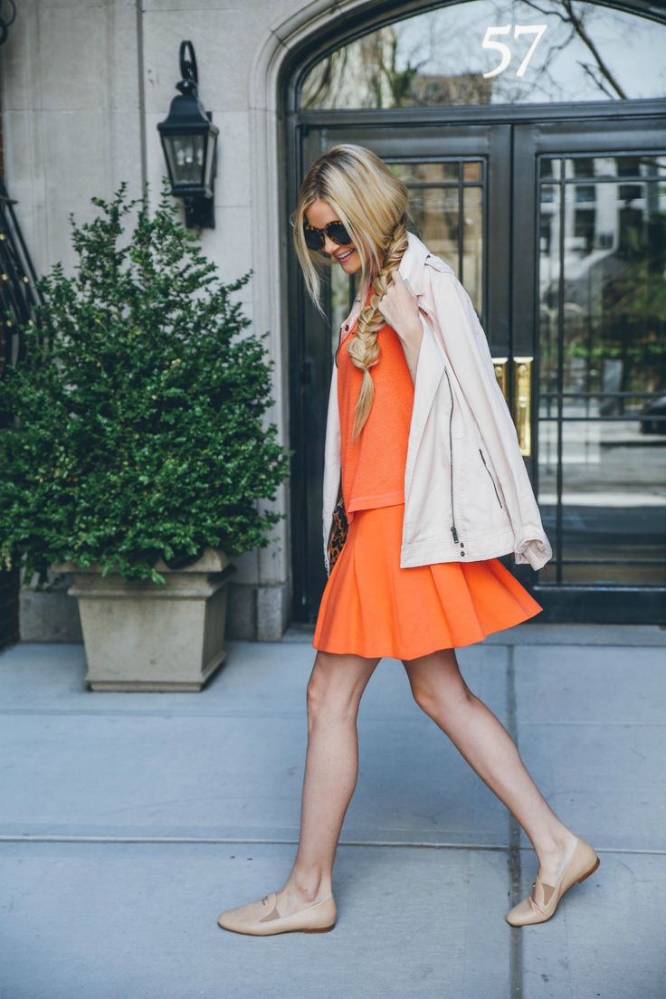 Amber Fillerup Clark is wearing an orange top and skirt from Banana Republic