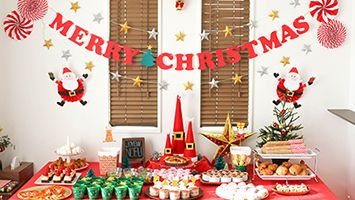 フードコーナーのクリスマス演出は、サンタが住む街にやって来たような世界観をイメージ。    フードコーナーの演出は、サンタが住む街にやってきた様な世界観をイメージして飾り付けをしてみました。赤いテーブルクロスの上にサンタモチーフのクリスマスオブジェを中心に置き、フードの他にも星のオーナメントやクリスマスツリーなどの飾りも置いてみたりして、サンタが住む街を演出しています。 「MERRY CHRISTMAS」のガーランド素材はこちら>> 渦巻きペーパーファンの作り方&素材はこちら>> キラキラ立体星ガーランドの作り方はこちら>>   フードコーナーの演出の中心に置いたサンタモチーフのクリスマスオブジェ。大中小3つの違う大きさの円錐発砲スチロールにフェルトを巻き付けたりして作っています。周りには松ぼっくりやキラキラ星のワイヤーを巻き付けてサンタの街のシンボルのようなイメージで演出してみました。飾る時には下に空き箱を置いて高さを出しています。  サンタ風クリスマスオブジェの作り方はこちら>> パーティー料理は、サンタやツリーなど、クリスマスを感じさせるものをモチーフに見た目も演出。…