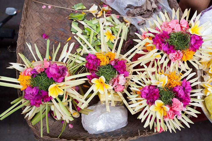 """Murmure des Dieux, o """"susurro de los dioses"""" es una ilustración del sacrificio ritual hindú, o canang sari, como se le llama en Bali. Estas ofrendas se pueden encontrar en la isla casi todo el día y en muchos lugares diferentes. Puede encontrarse con ellas fácilmente: es una pequeña cesta, tejida a partir de hojas de palma y decorada con flores de colores, arroz, caña de azúcar, especias y rociada con agua bendita y rematada con incienso - todo esta presentación puede ser considerada como…"""