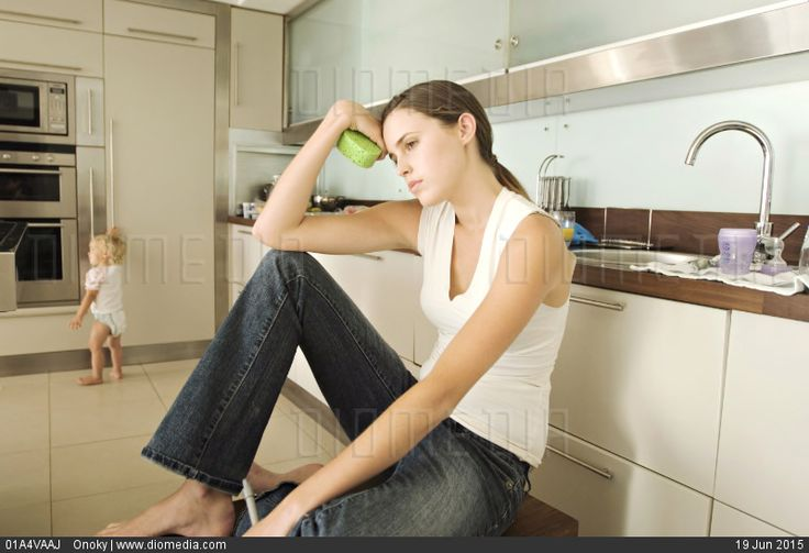 Sad young woman sitting in kitchen, little girl in background, indoors - stock photo