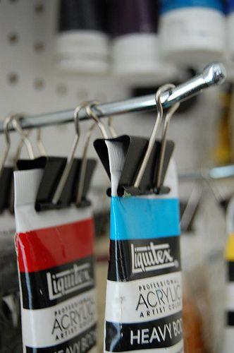 Do it just like they do at the art store! This is an easy way to organize and store your paints so that they don't take up a lot of space. (Great for artists living in a small space!)  you'll need : a peg board peg board rods, hooks, etc. binder clips  (you can find your pegboard and accessories at most hardware store.)  this is really simple and easy. just put your peg board up and put all your rods & hooks where you want them on the board. then take your binder clips and clamp y...
