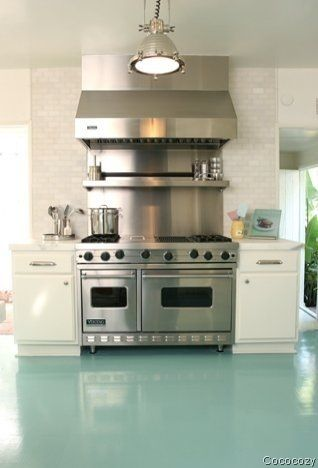 perfect kitchen. the chrome stove with the polished cement floor colour. love.