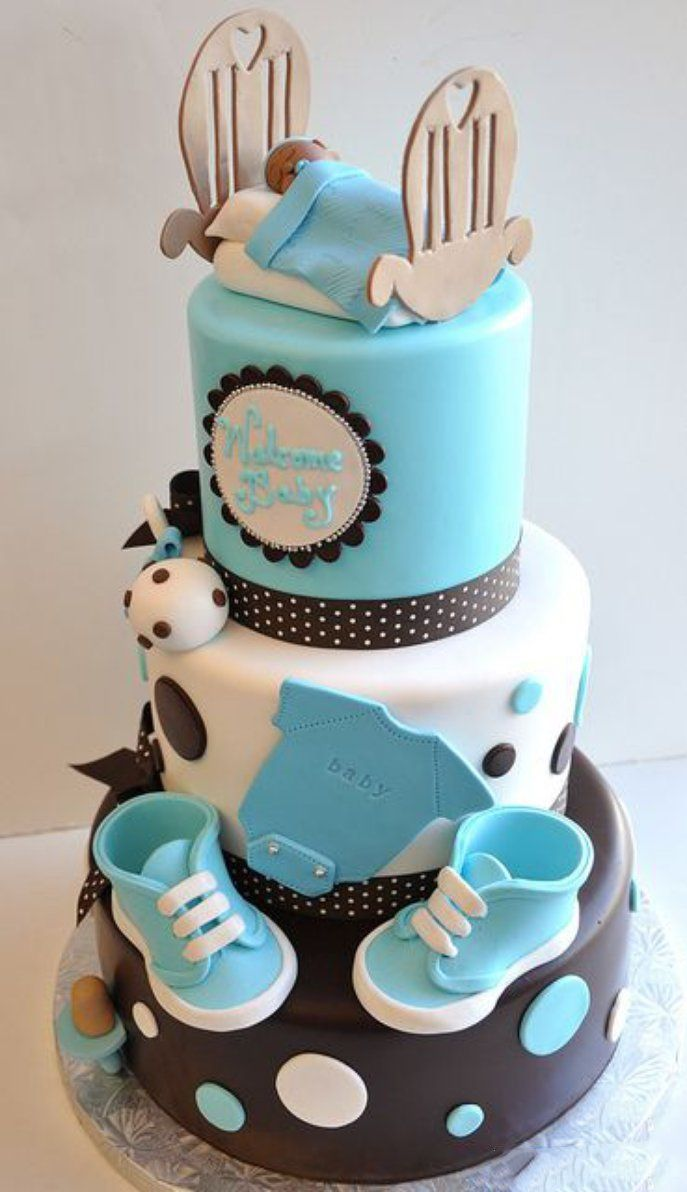 Pastel de tres pisos en color azul y café con decoraciones de ropita de bebé