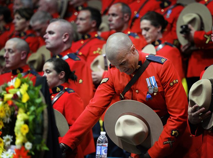 RCMP officers react as they attend the regimental funeral of three slain officers at the Moncton Coliseum in Moncton, N.B. on Tuesday, June 10, 2014. Const. David Ross, Const. Fabrice Georges Gevaudan and Const. Douglas James Larche were killed in a shooting spree last Wednesday.