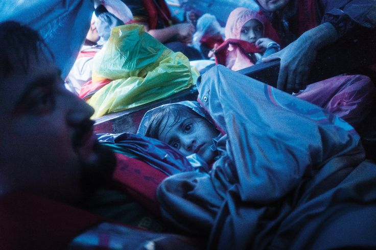 In the early morning hours on the first day of their journey, the asylum seekers crowded together under a tarp. PHOTOGRAPHS BY JOEL VAN HOUDT