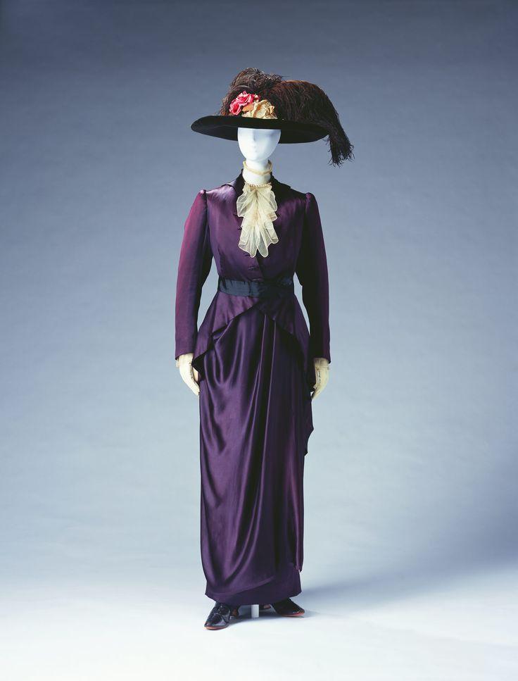 Day Dress by Pierre Bulloz, 1910, Deep purple silk satin; set of jacket, bodice, and skirt; black silk faille belt; white cotton tulle jabot on bodice.