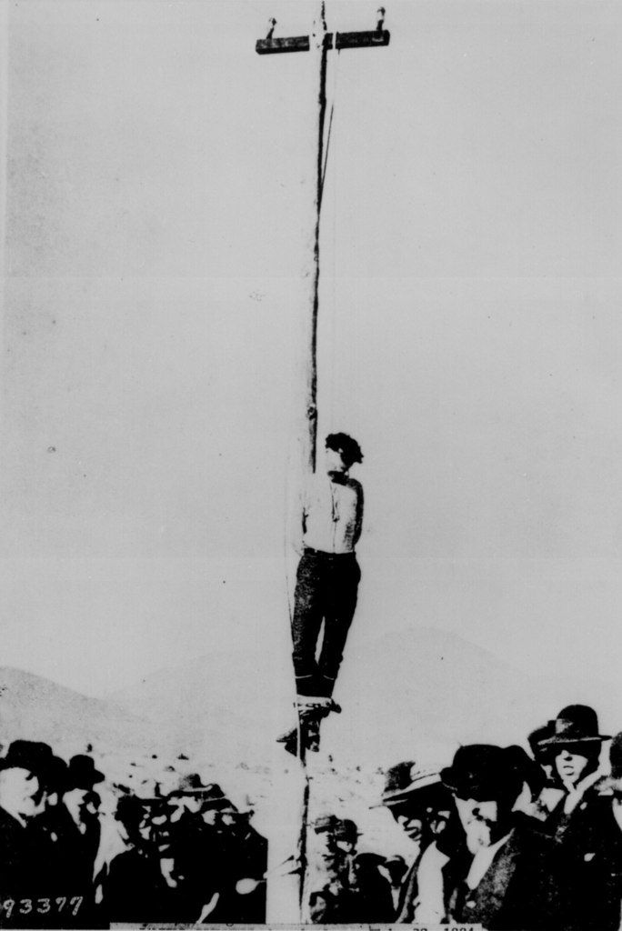 frontier justice, hanging from a telegraph line pole