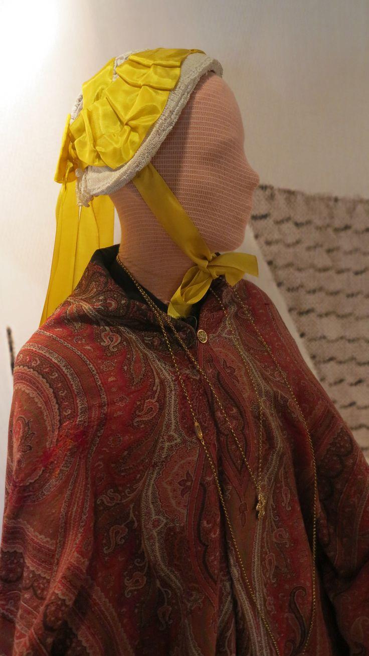 Belgische muts uit Baarle-Nassau voor ongetrouwde vrouwen. Het gele lint is vervangen, aangezien het oude vergaan was. Hier is smaller lint genomen en 2 breedtes aan elkaar gezet. Zij draagt hierbij een kasjmier shawl, en een lange gouden ketting met emaille versierd bloemetjesslotje. Onderaan een kruis.