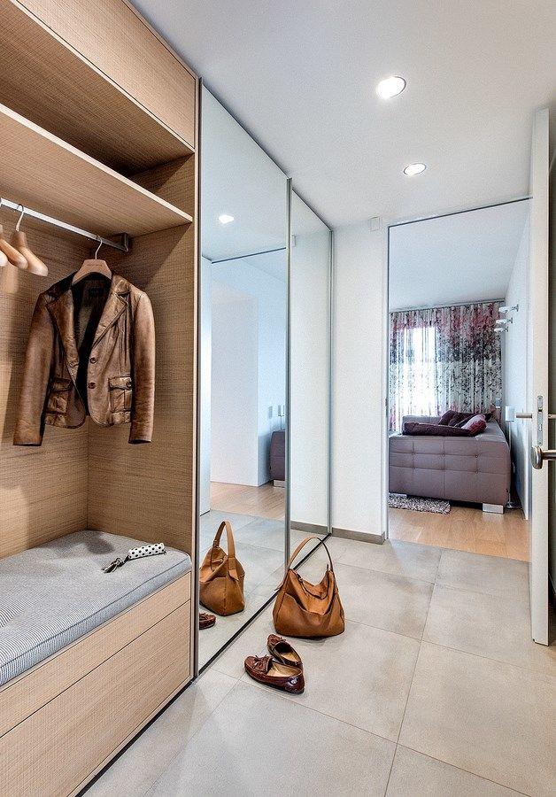 Velmi praktické řešení úložných prostorů zhotovených na míru umožňuje usednutí na lavici pod věšákem. Komfort zajišťuje podlahové vytápění. Zrcadlová čela skříní opticky zvětšují úzký prostor chodby.