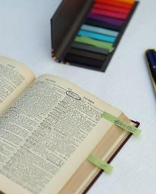 A century-old dictionary with colored pencils for family and friends to flag encouraging words with rainbow-hued tags, creating a meaningful, long-lasting memento for the happy couple.