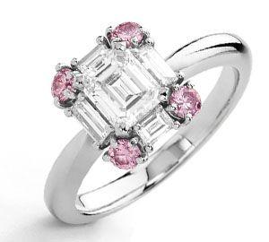 Cornerstone pink diamond ring with one emerald cut white diamond and baguette cut white diamonds.