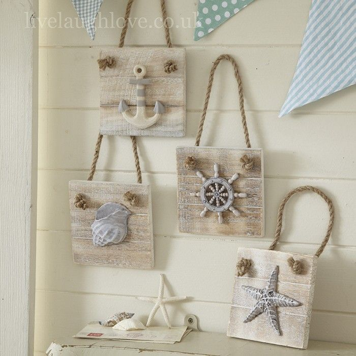 A set of 4 lightly whitewashed wooden wall plaques which hang from chunky rope. 1 Anchor, 1 Ships wheel,1 shell and 1 starfish. Would look great in a nautical themed room.