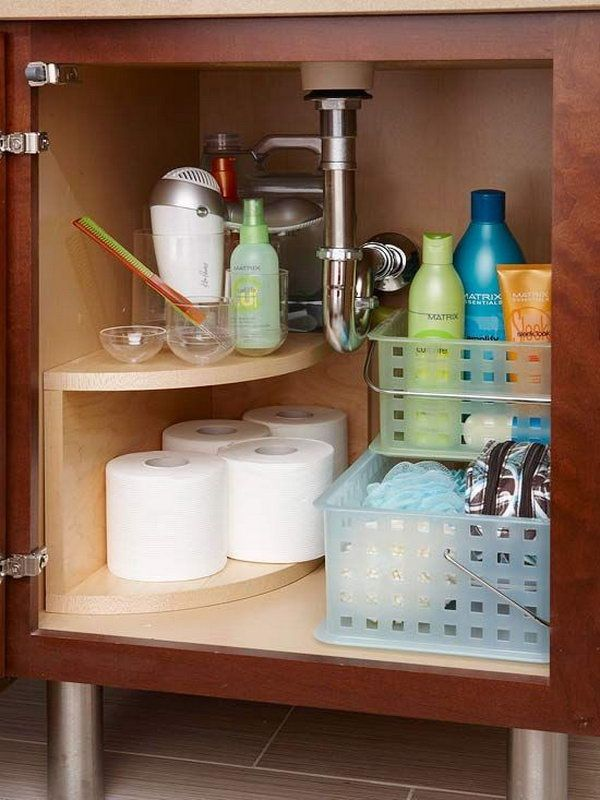Install a curved multitier storage unit along the undersink plumbing. Free up space for everyday items in the vanity of the bathroom.