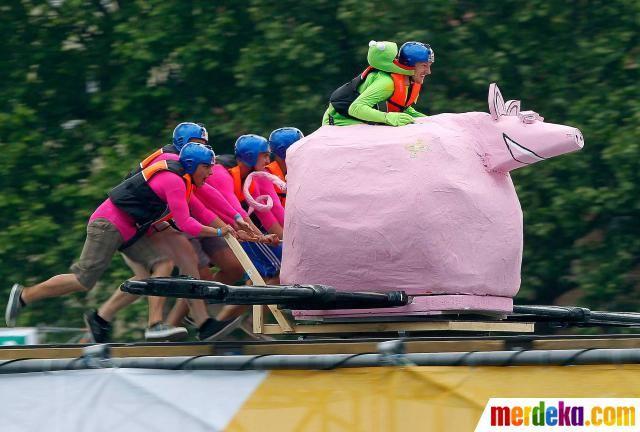 Sejumlah peserta mendorong rekannya yang naik di atas boneka hewan pada festival Red Bull di Mainz, Jerman.
