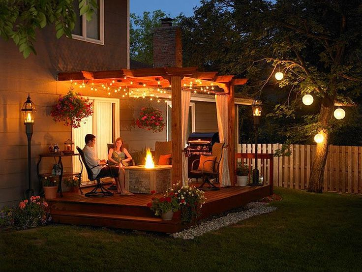 Twinkling outdoor lights lend this backyard deck an almost magical quality. Heat lamps modeled after antique lanterns complete the look. #firepit #fireplace #patio