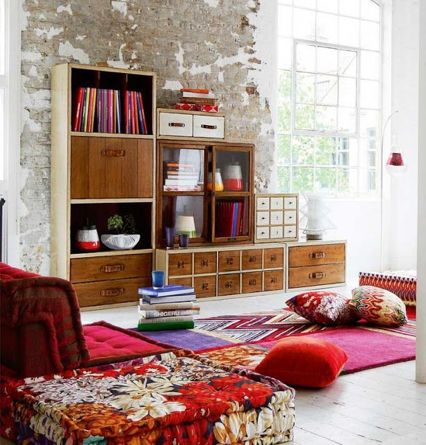 It's all in the elements...exposed brick, modern bookcase, vivid textiles, pop of florals...