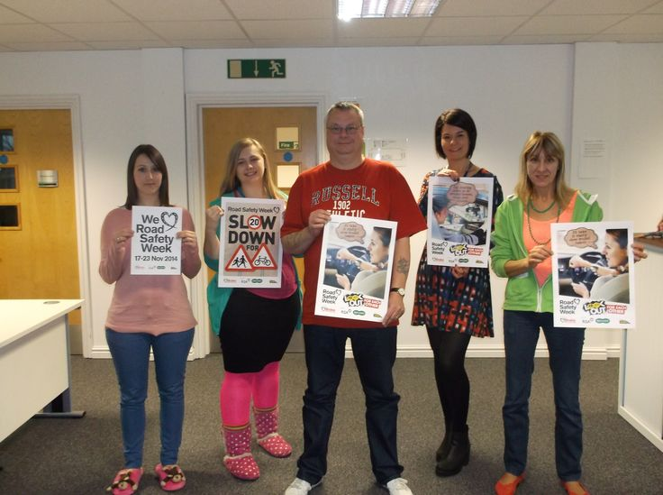 Spencers team in bright clothes holding Bright Day posters