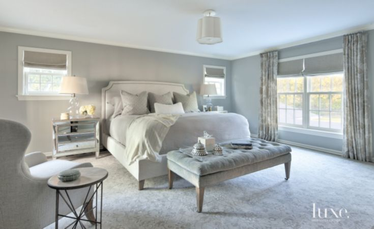 The master bedroom features Holland & Sherry drapery fabric. An upholstered bed by Lee Industries, purchased through Kate Marker Interiors, is covered in a quilted coverlet with custom accent pillows from bedside manor. Nightstands are by Bethel International.