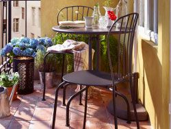 A sunny balcony with grey table and chairs combined with a semi-circular parasol.