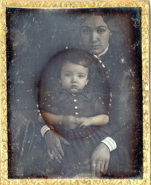 When the mat that framed the portrait of the child was removed, the woman holding the child was revealed