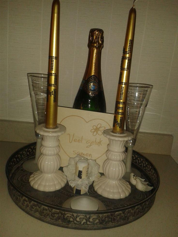 fles champagne met trouwdatum op, 2 glazen, 2 kandelaars met goudkleurige kaarsen met de naam van bruid en bruidegom, geursteen en geurtje, 3 witte bloemen en witte duiven met trouwring, houten wenskaart