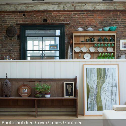 Die rote Ziegelsteinwand gibt dem Raum ein charmantes Loft-Flair. Mit einer Vintage-Holzbank und einem abstrakten Wandbild wird die Wohnküche zu einem  …
