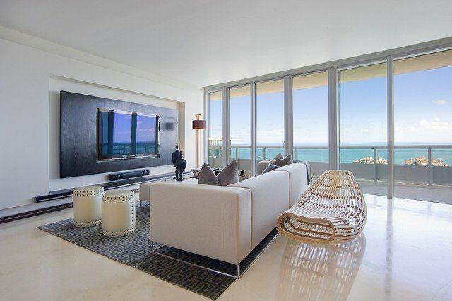 idées aménagement salon ultra moderne avec écran TV plasma à fixation murale, canapé blanc et tapis gris