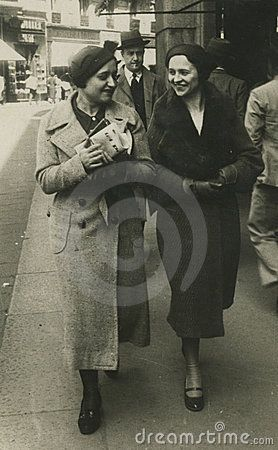 This original antique photograph is taken in 1945. Two girls chatting and walking in the street.